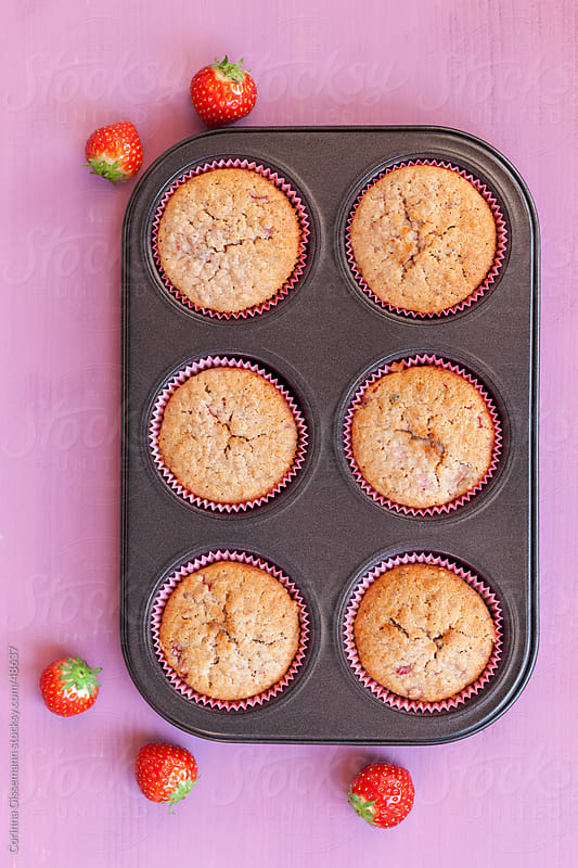 fresh baked strawberry muffins in a tin on table with fresh strawberries  by Corinna Gissemann for Stocksy United