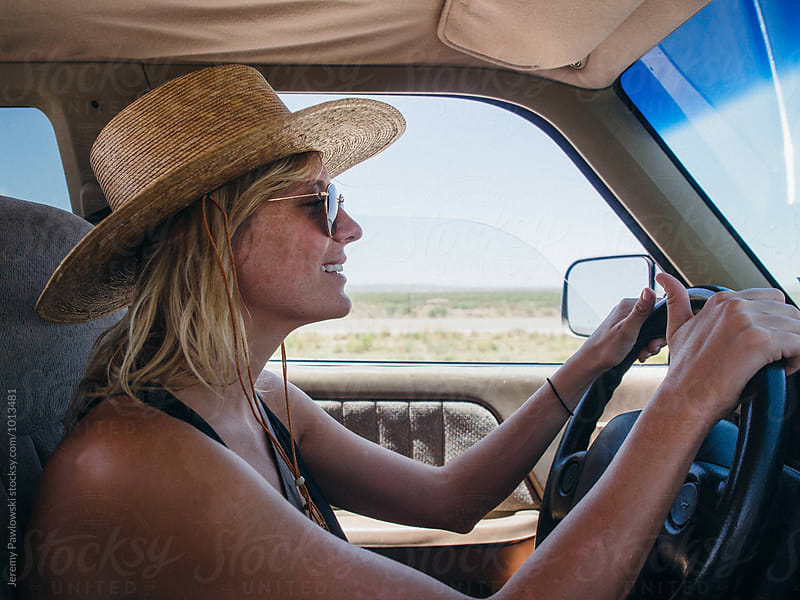 Girl in straw hat driving pickup truck on road trip by Jeremy Pawlowski for Stocksy United