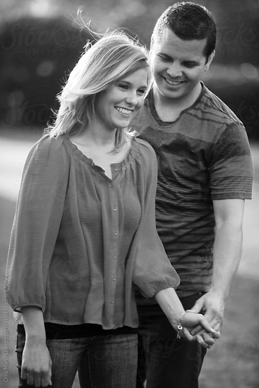 Happy couple holding hands and smiling  by Dina Giangregorio for Stocksy United