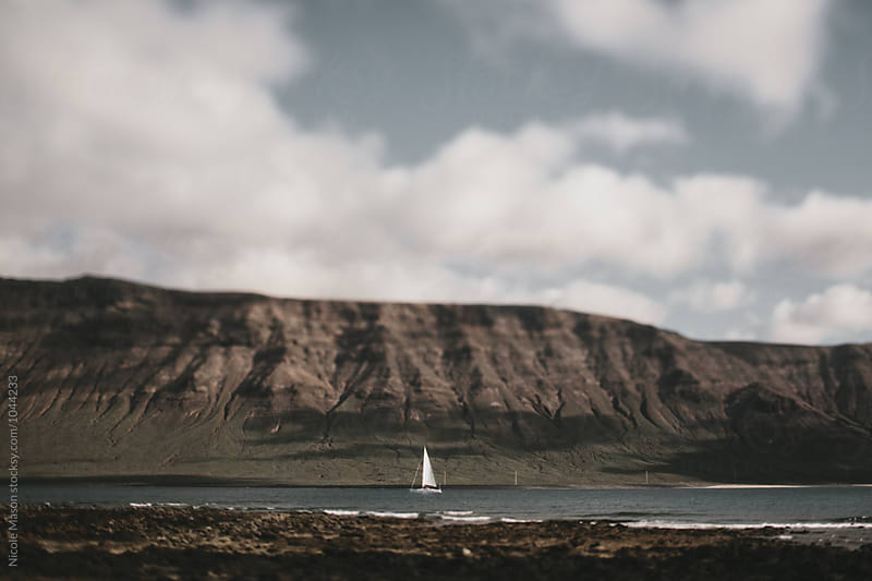 sailboat on water in front of rocky coast line by Nicole Mason for Stocksy United