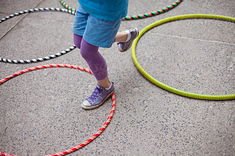 young girl jumps across hula hoops on the ground by Natalie JEFFCOTT for Stocksy United