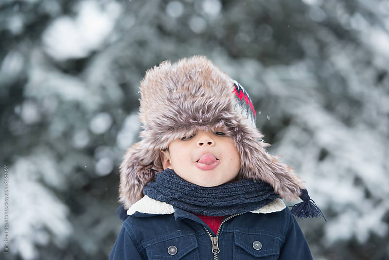 child trying to catch snowflakes on his tongue by Tara Romasanta for Stocksy United