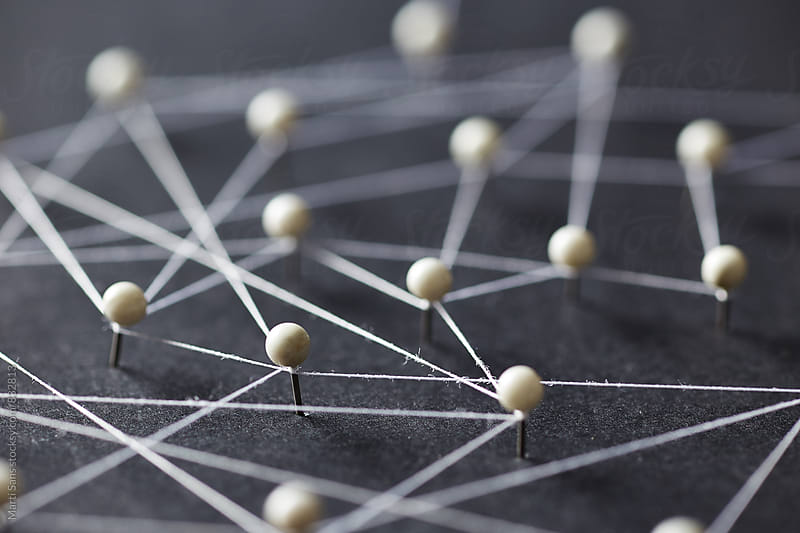 Close-up of white pins on black background creating a network by Martí Sans for Stocksy United