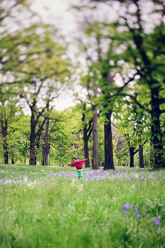 Boy running through field of bluebells by Angela Lumsden for Stocksy United