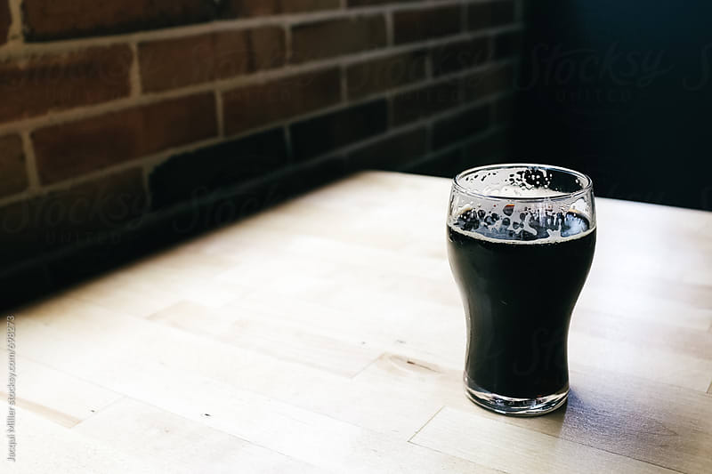 Half pint of stout on a table with copyspace - horizontal  by Jacqui Miller for Stocksy United