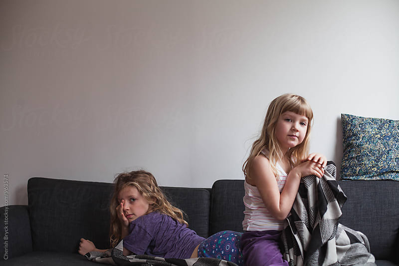 Sisters cuddle on the couch. by Cherish Bryck for Stocksy United