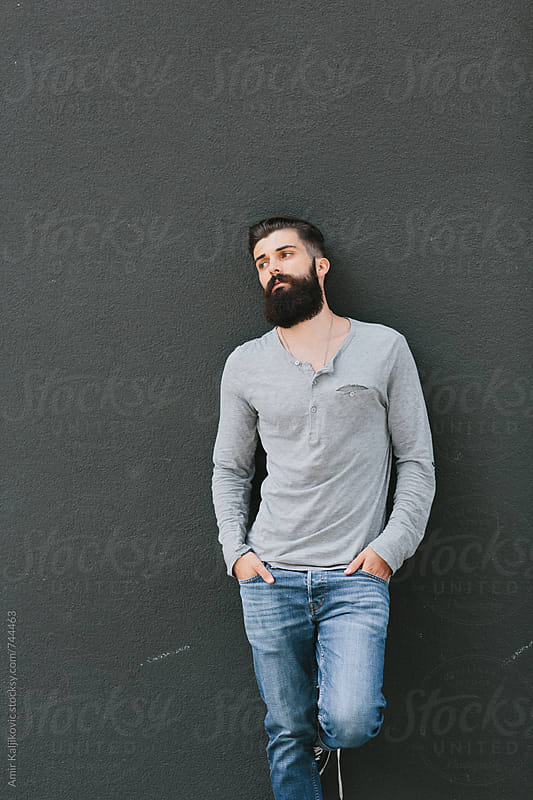 Handsome young bearded man leaning against a wall by Amir Kaljikovic for Stocksy United