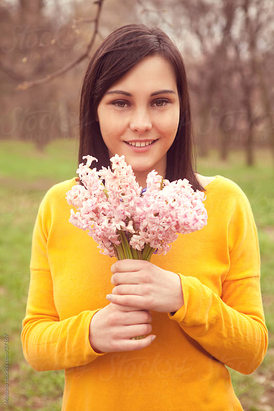 Young woman in park posing with bouquet of flowers. by Mosuno for Stocksy United