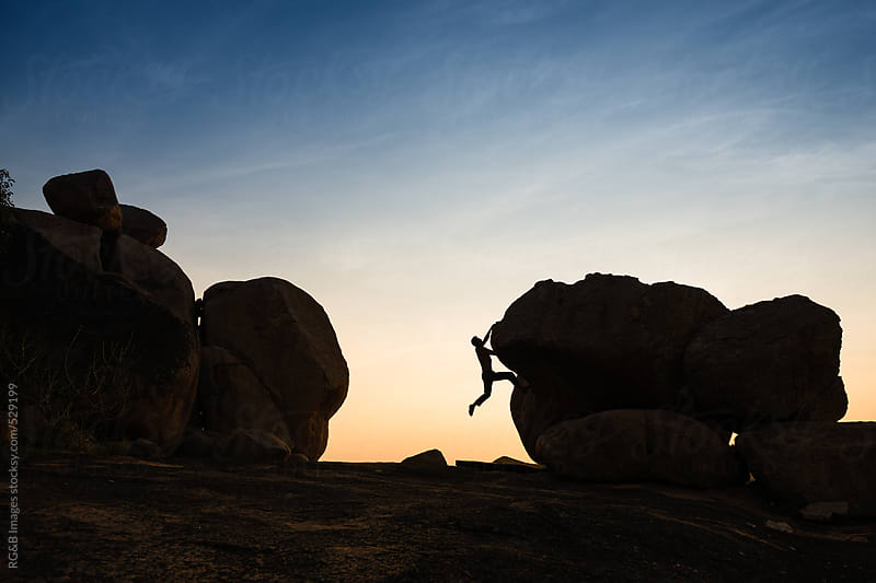 Man silhouette bouldering in the sunset by RG&B Images for Stocksy United