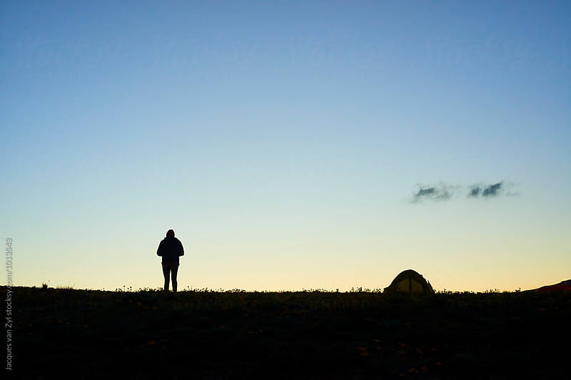 Silhouetted camper walking back to her tent at dusk. by Jacques van Zyl for Stocksy United