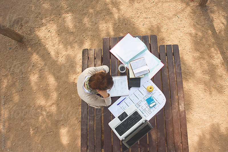 Aerial view of young woman studying on a park table with laptop. by BONNINSTUDIO for Stocksy United