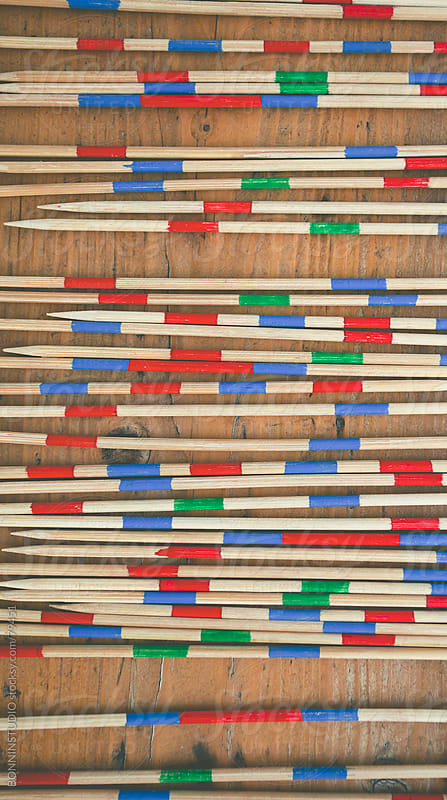 Mikado game. Colorful wood sticks on old wooden background. by BONNINSTUDIO for Stocksy United