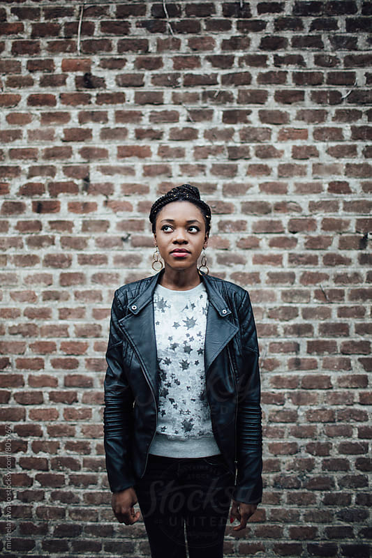 Young African woman standing with a brick wall in the background by michela ravasio for Stocksy United