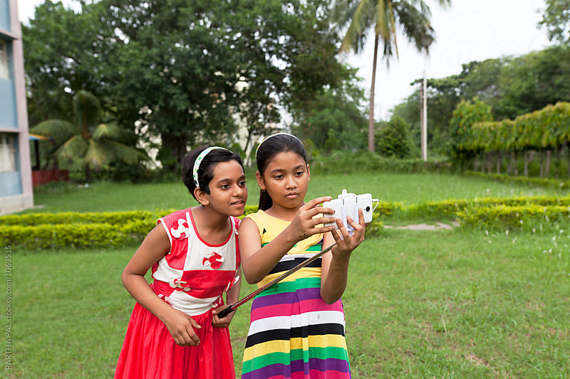 Teenage girls setting smartphone for takng selfie by PARTHA PAL for Stocksy United