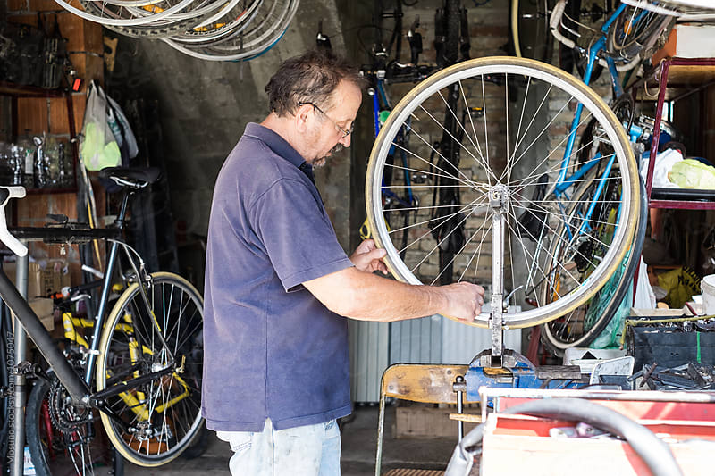Mechanic Repairing a Bike  by Mosuno for Stocksy United