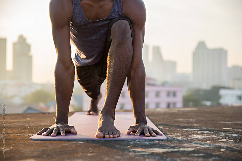 Closeup of a man doing yoga on a city rooftop  by Jovo Jovanovic for Stocksy United