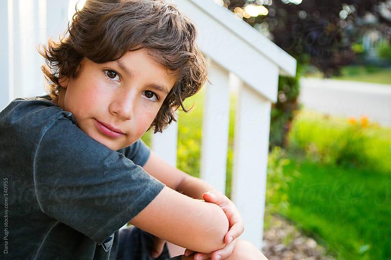 boy on porch by Dana Pugh for Stocksy United