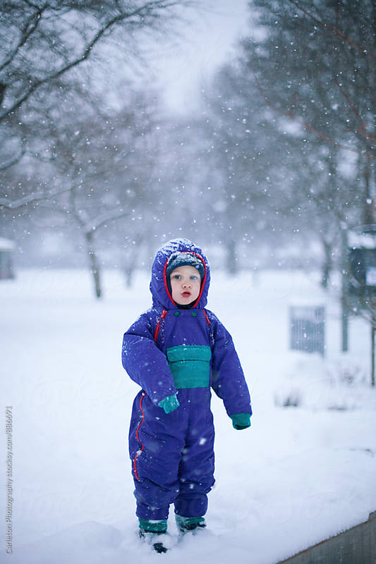 Boy in snowsuit enjoying falling snow by Carleton Photography for Stocksy United