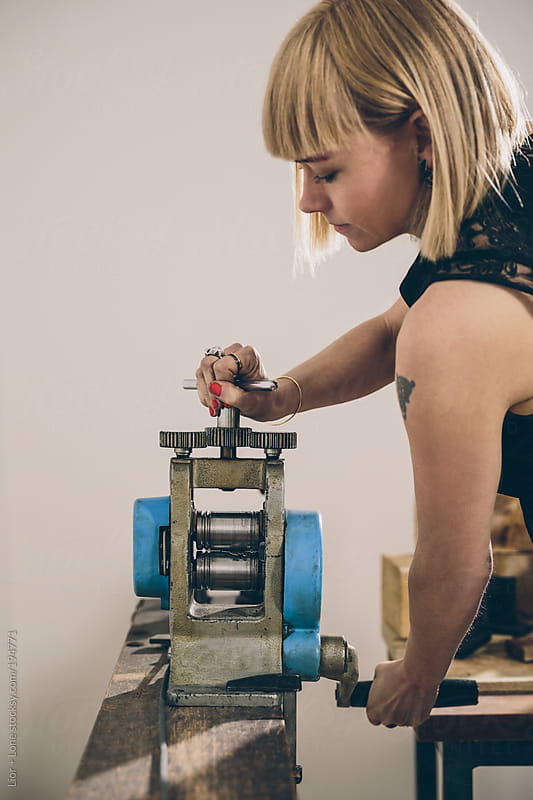 A young attractive jewelry designer handling a metal press  by Lior + Lone for Stocksy United