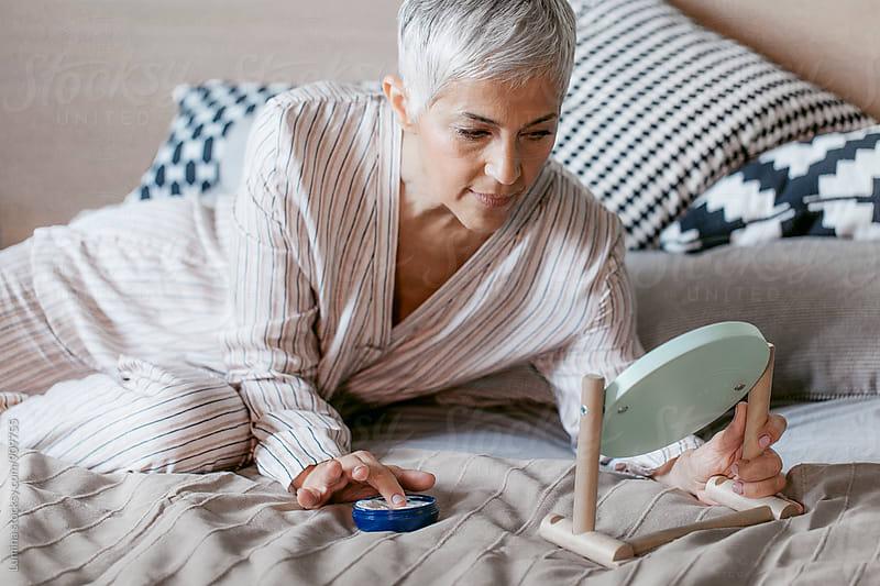 Senior Woman Applying Cream to Face by Lumina for Stocksy United