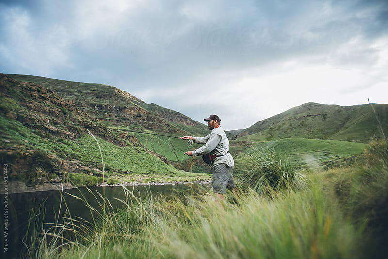 fly fisherman casting into a wilderness river by Micky Wiswedel for Stocksy United