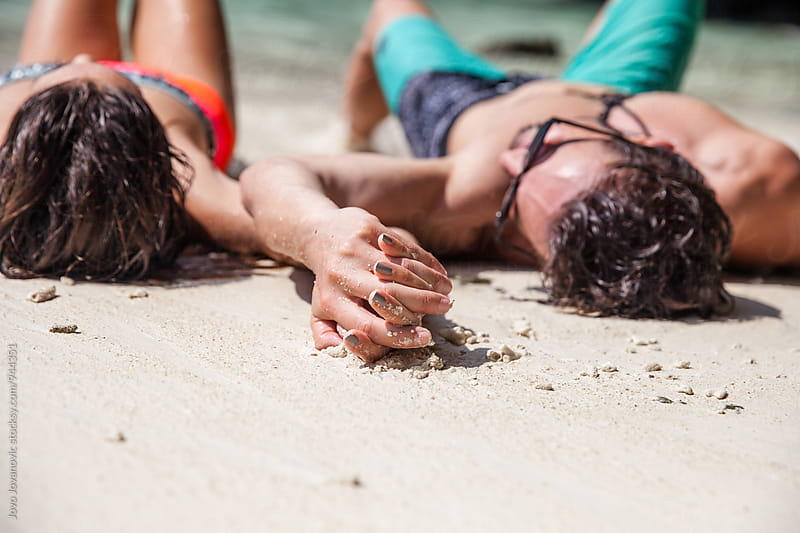 Attractive couple relaxing on sandy beach, holding hands by Jovo Jovanovic for Stocksy United