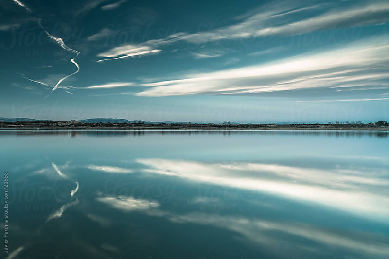 Sunset on the big lake reflecting clouds by Javier Pardina for Stocksy United