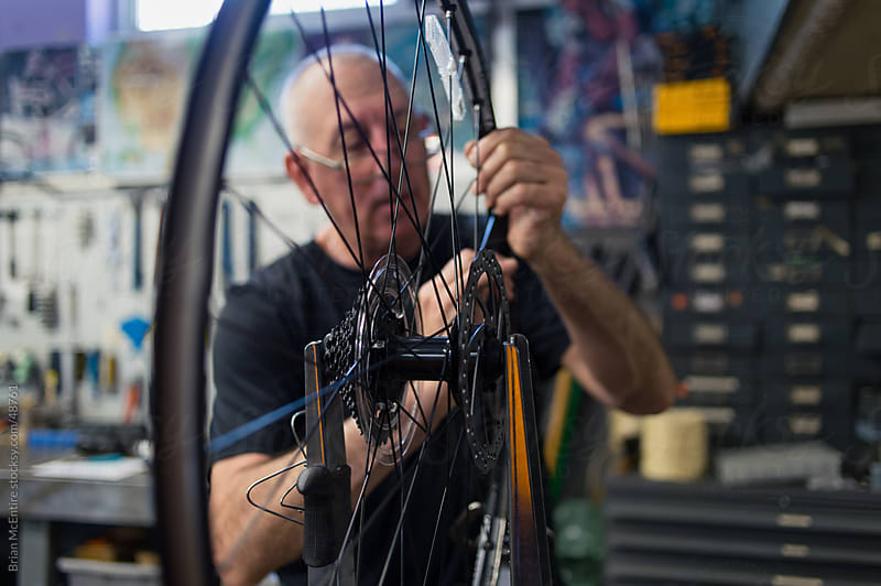 Local Bike Shop: Store Owner Trues Wheel of New Bicycle During B by Brian McEntire for Stocksy United