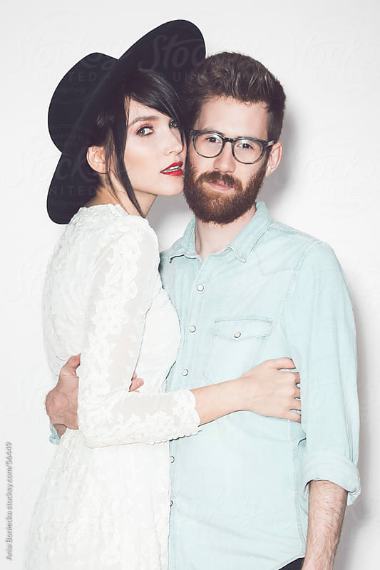 Stylish couple holding eachother on white background by Ania Boniecka for Stocksy United