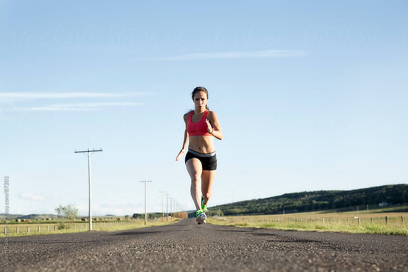 a young fit woman sprinting on a paved road by Shaun Robinson for Stocksy United