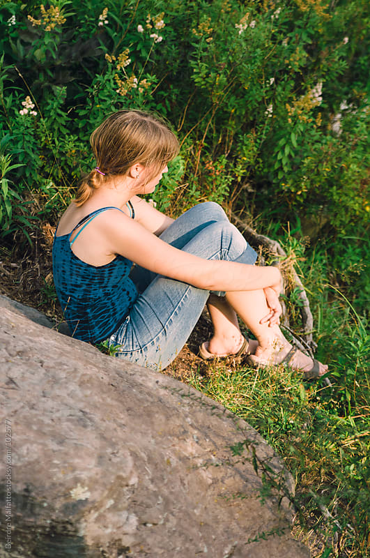 young teen girl sitting on rock by Deirdre Malfatto for Stocksy United