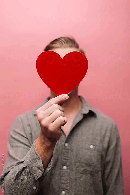 Man with a heart covering his face by Kayla Snell for Stocksy United