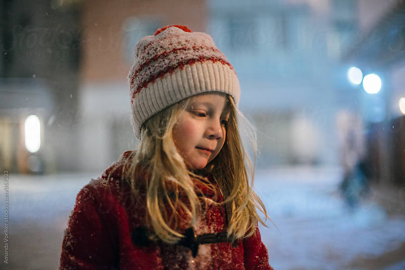 Portrait of  A young Girl at night in a Snowstorm by Amanda Voelker for Stocksy United