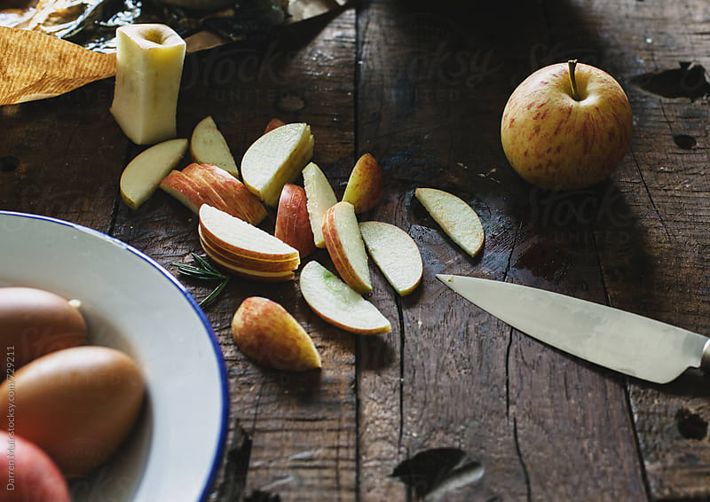 Sliced apples on a wooden table. by Darren Muir for Stocksy United