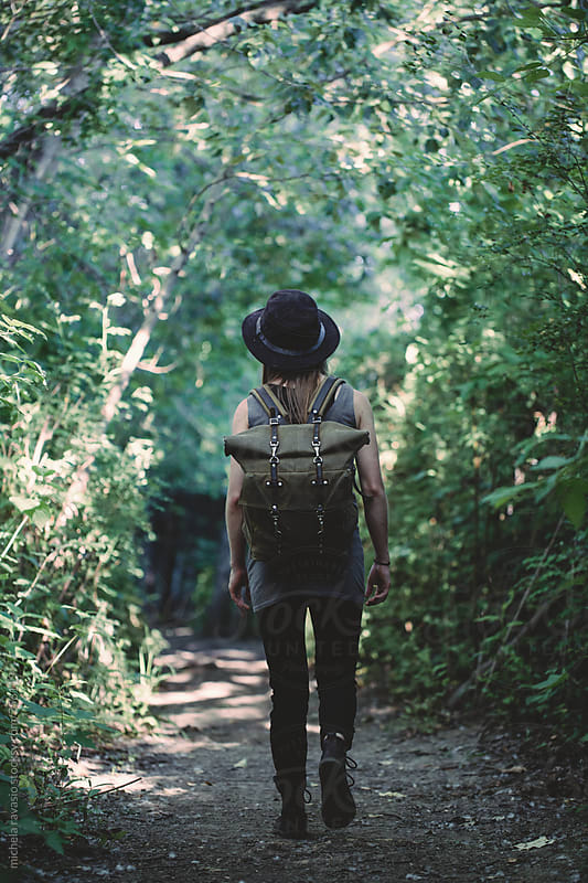 Woman backpacker walking in the forest by michela ravasio for Stocksy United