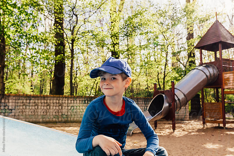 Preschooler boy on playground smiling into camera by Mima Foto for Stocksy United