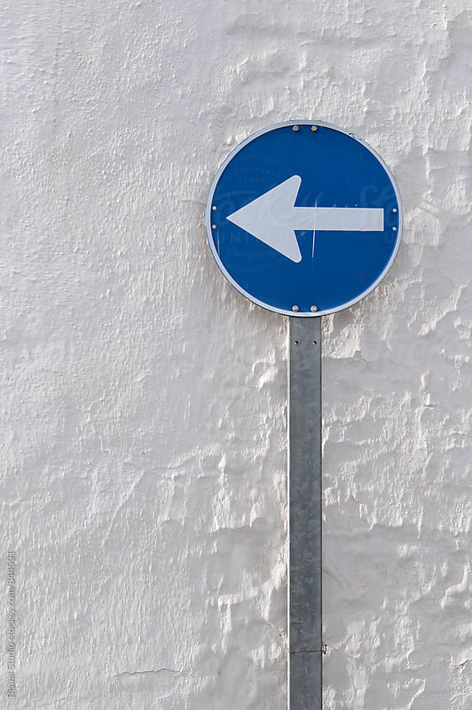 Directional Sign on a white old wall by Bisual Studio for Stocksy United