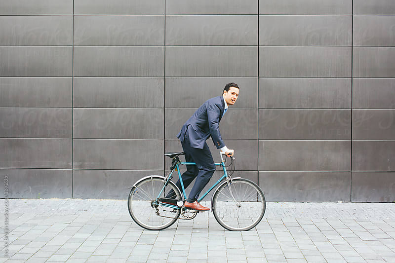 Young businessman biking while looking in the camera by Ivo de Bruijn for Stocksy United