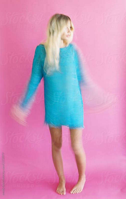 blonde girl moving slow shutter pink background by wendy laurel for Stocksy United