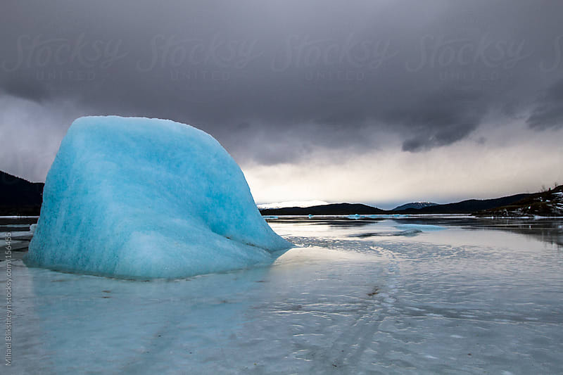 Blue iceberg frozen in place in ice-covered lake by Mihael Blikshteyn for Stocksy United