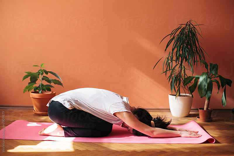 Woman having home yoga class by VeaVea for Stocksy United