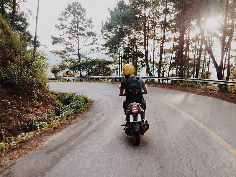 Riding motorcycle through thialand on an adventure by Jesse Morrow for Stocksy United