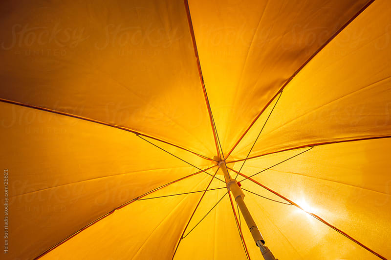 a yellow umbrella under the sun by Helen Sotiriadis for Stocksy United
