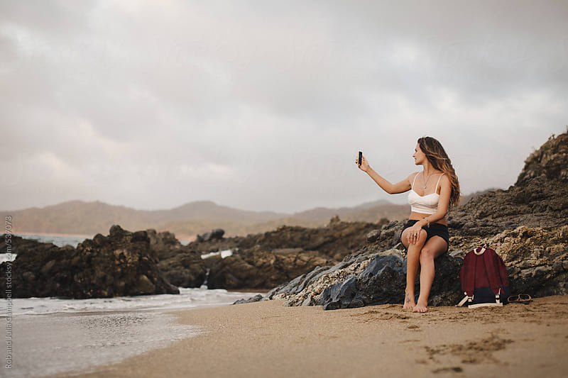 Pretty young girl hanging out at beach at sunset, taking picture with mobile phone by Rob and Julia Campbell for Stocksy United