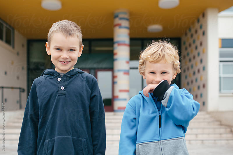 Two smiling young boys standing together in front of a school by Ania Boniecka for Stocksy United