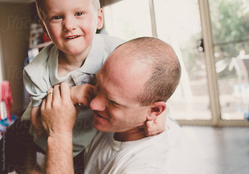 Father and Son Playing on the Floor by Gary Radler Photography for Stocksy United
