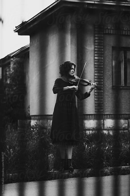 Beautiful young woman standing in the street playing violin by Natasa Kukic for Stocksy United