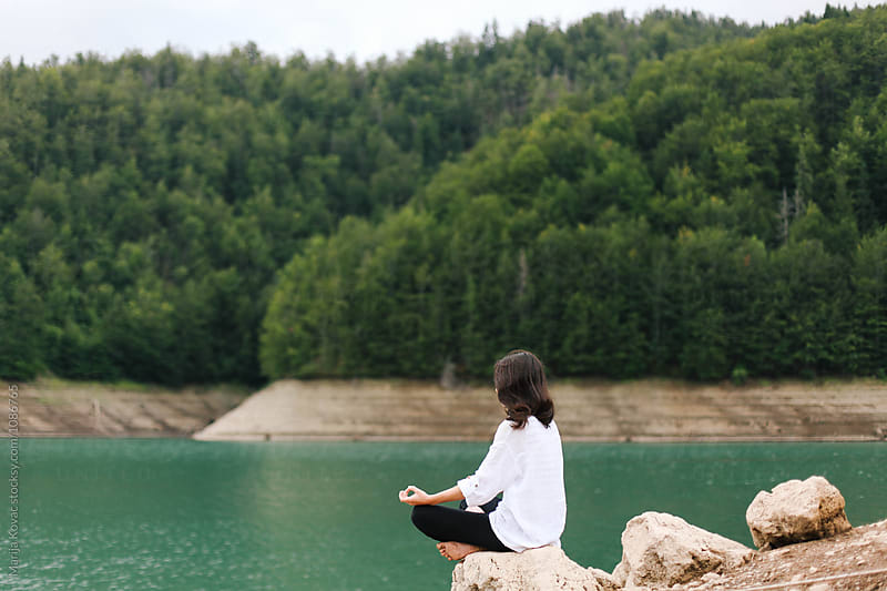 Woman meditating, sitting on the rock, from behind by Marija Kovac for Stocksy United