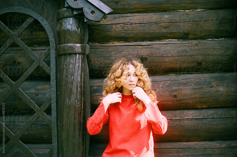 A portrait of young redhead woman in front of old russian wooden house by Anna Malgina for Stocksy United