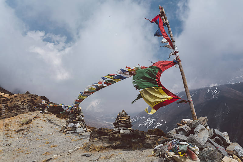 Prayer flags flying on the wind in Himalayas  by Dejan Ristovski for Stocksy United